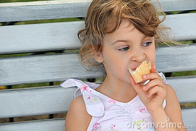 Little girl sits and eats ice-cream Stock Photo