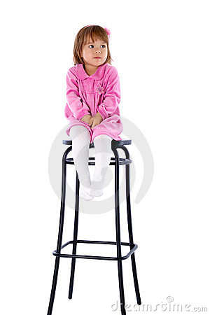 The little girl sits on a high chair