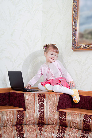 Little girl sits with a laptop
