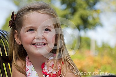 A little girl sits on a park bench