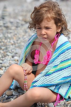 Little girl sits on pebble