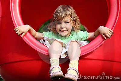 Little girl sits in plastic hole on playground