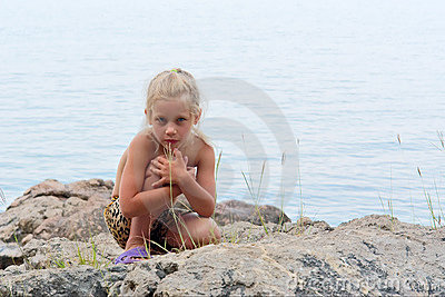 Little girl sits on rocks next to sea