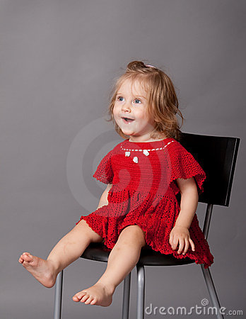 Little girl is sitting in chair in studio