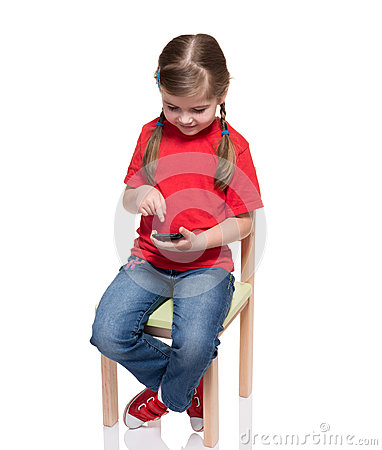 Little girl sitting on a chair and using smartphone