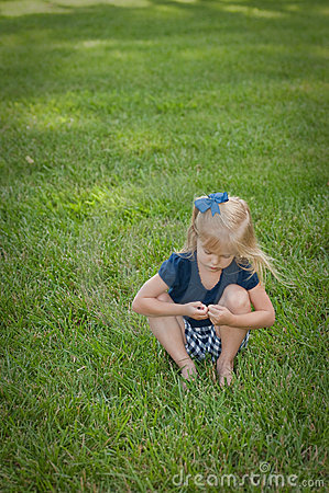 Little girl sitting in grass