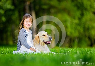 Little girl sitting on the grass with labrador retriever