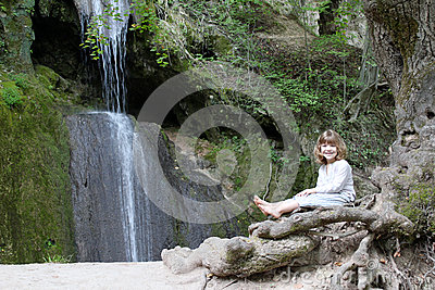 Little girl sitting next to a waterfall
