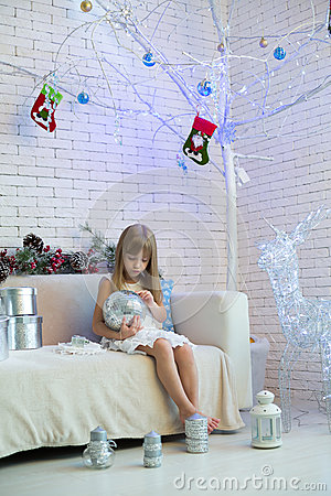 Free Little Girl Sitting On The Sofa With Christmas Gifts And Playing Stock Photo - 32483480