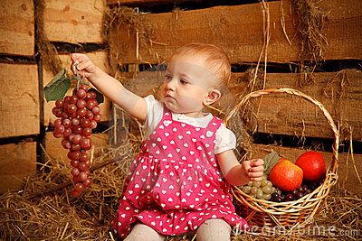 Little girl is sitting on pile of straw with grape
