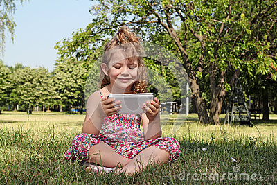 Little girl sitting play with tablet