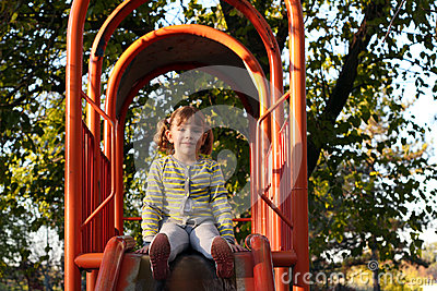 Little girl sitting on playground slide