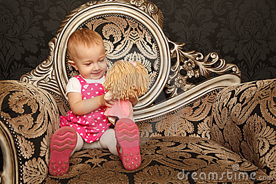 Little girl sitting on retro armchair with doll