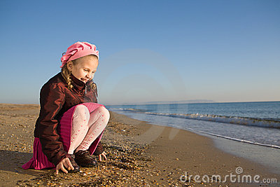 Little girl sitting by the sea
