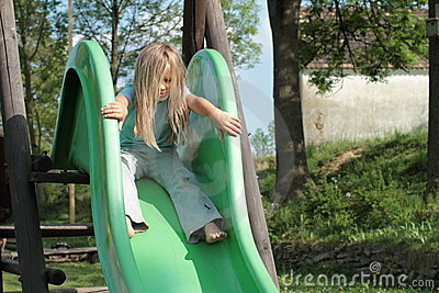 Little girl sitting on a slide