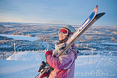 Little girl-skier on the hill watching the sunrise