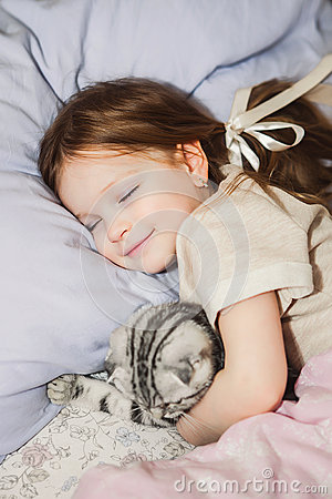 Little Girl Sleeping In Bed With Her Cat Stock Photo