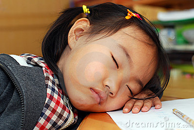 Little girl is sleeping near her homework