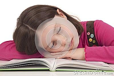 Little girl sleeping on a open book