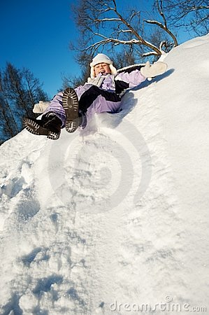 Little girl sliding in the snow