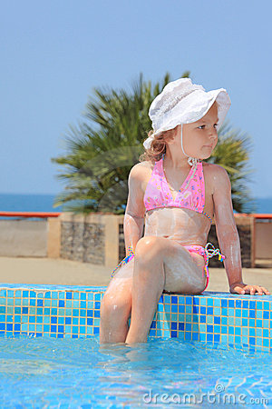 Little girl smeared with cream for sunburn on pool
