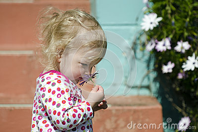 Little girl smell flower