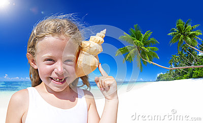 Little Girl Smiling at Camera by the Beach with Seashell Against her Ears Stock Photo