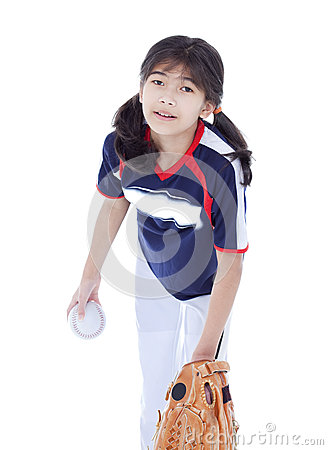 Little girl in softball team uniform ready to throw a pitch
