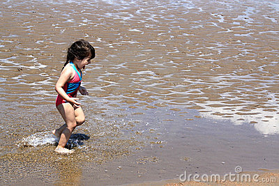 Little girl splashing and playing at the beach