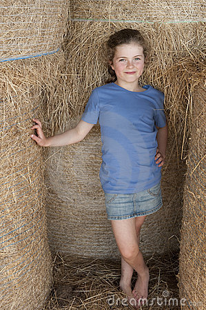 Little girl standing amongst bales of hay