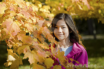Little girl standing by autumn leaves