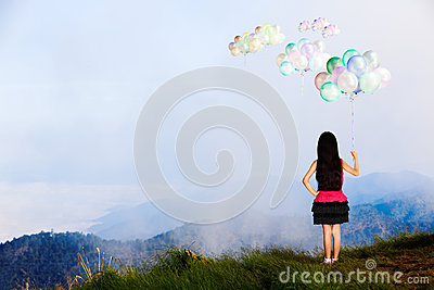 Little girl standing at high mountain and looking balloon