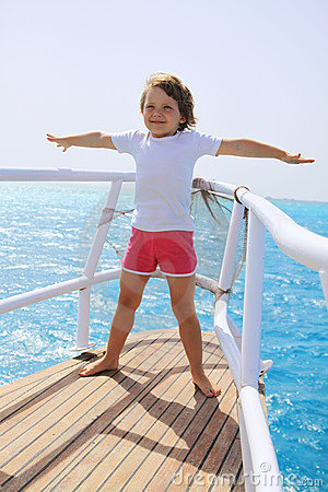 A little girl standing at the stern of the ship