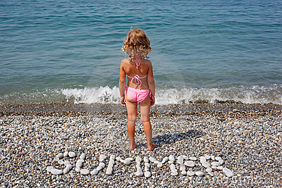 Little girl stands on beach near water.