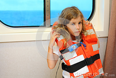 Little girl stands in cabin of ship