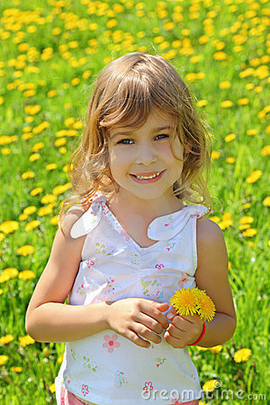 Little girl stands on  field and holds dandelions