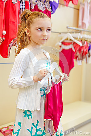 Little girl stands holding hanger with closed swimsuit