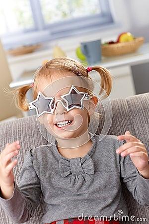 Little girl in star shaped glasses smiling