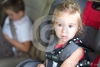 Little Girl Strapped Into A Childs Safety seat