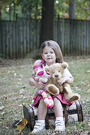 Little girl with stuffed bear and sock monkey