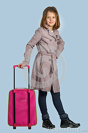 Little girl with a suitcase is preparing to travel