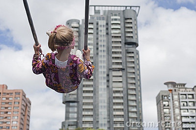 Little girl swinging in the city