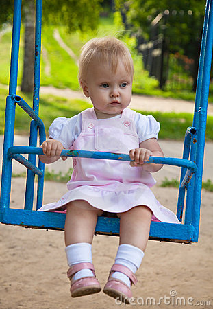 Little girl swinging in a playground