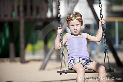 Little girl swinging on playground