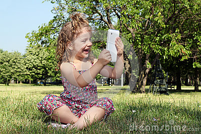 Little girl with tablet in park