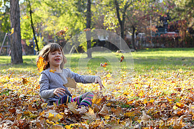 Little girl throws autumn leaves
