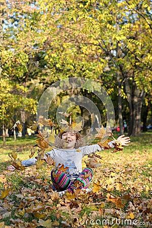 Little girl throws autumn leaves