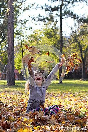 Little girl throws leaves