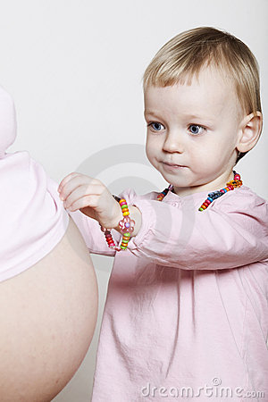 Little girl touching pregnant belly