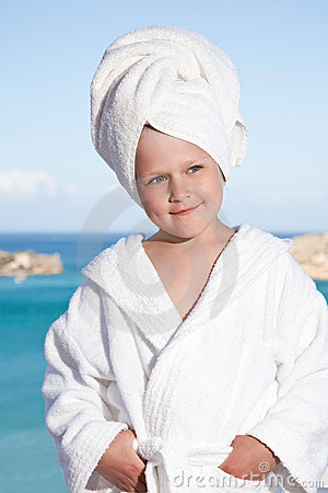 Little girl with towel on head in white bathrobe